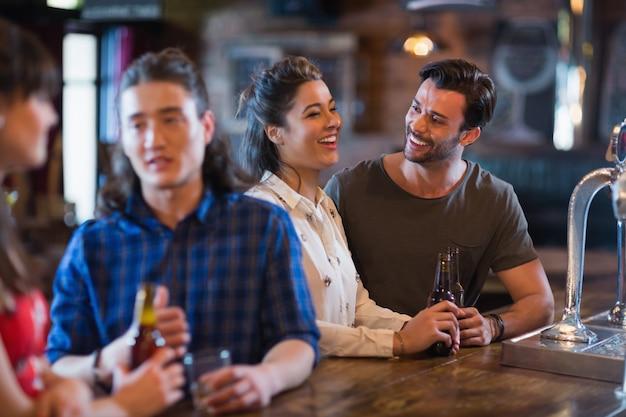 Amigos alegres interagindo no balcão do bar