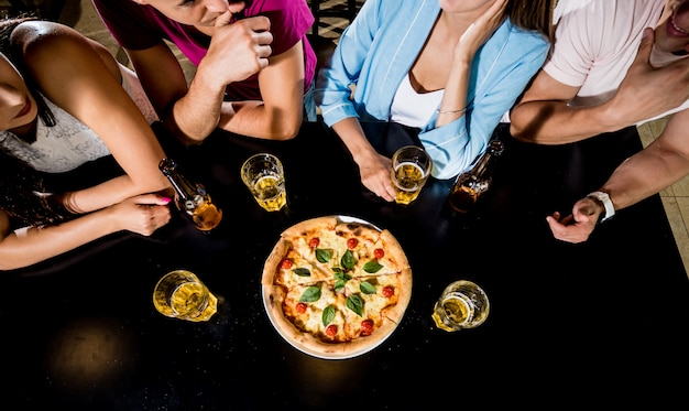 Amigos alegres no bar. bebendo cerveja, comendo pizza, conversando, se divertindo.