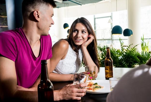 Amigos alegres no bar. bebendo cerveja, conversando, se divertindo.