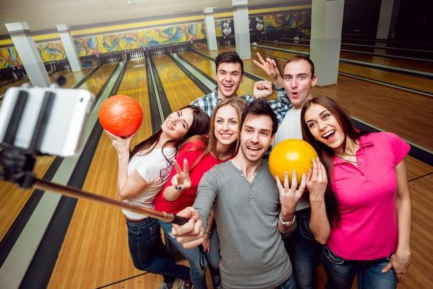 Amigos alegres no boliche com as bolas. Foto Premium
