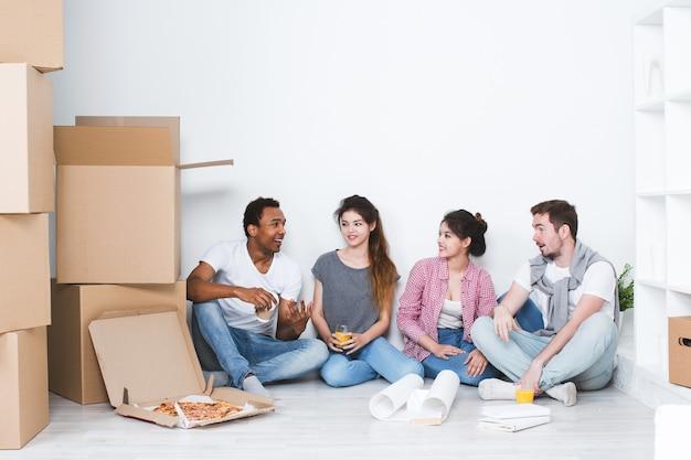 Amigos alegres se mudando para um novo apartamento