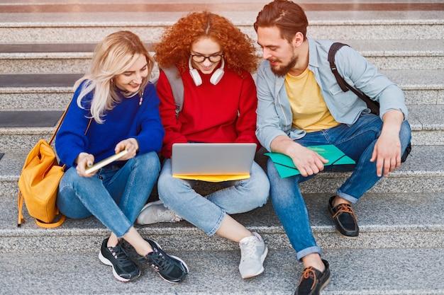 Amigos alegres sentados na escada preenchendo o formulário de inscrição para a faculdade