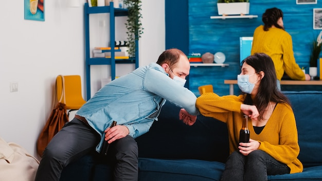 Amigos alegres sentados no sofá da sala de estar durante a nova festa normal fazendo nova saudação com cotovelo evitando a propagação do coronavírus