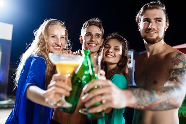 Amigos alegres, sorrindo, regozijando-se, descansando na festa perto da piscina