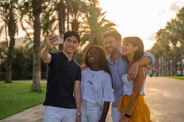 Amigos alegres tirando selfie perto das palmas das mãos
