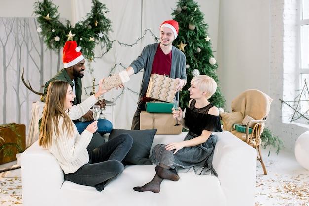 Amigos alegres trocando presentes na véspera de natal