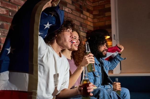 Amigos americanos bebendo cerveja enquanto torcem pelo time favorito no campeonato de futebol na tv, jovens estudantes gritando, gritando, comemorando a vitória