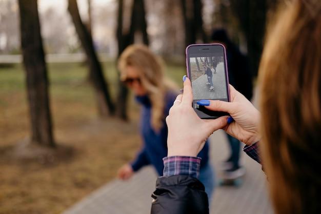 Amigos andando de skate no parque enquanto uma mulher tira fotos