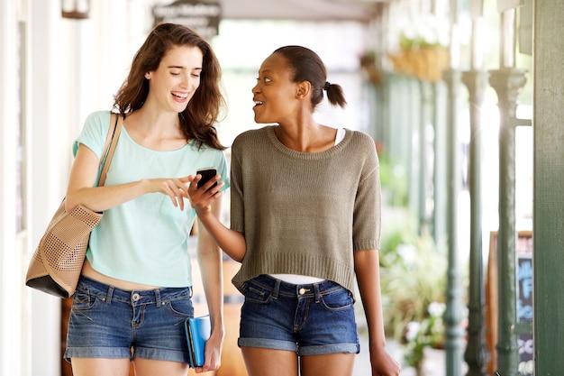 Amigos, andar, junto, usando, telefone móvel