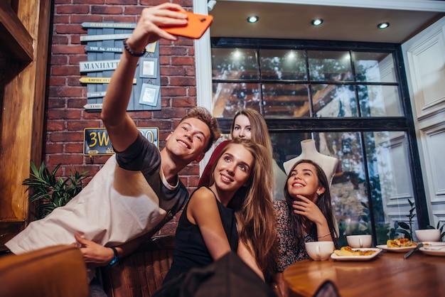 Amigos animados tomando selfie com smartphone sentado à mesa, sair à noite.