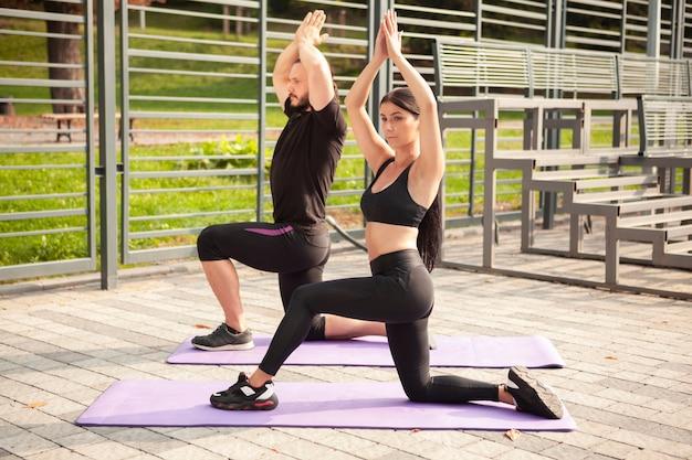 Amigos ao ar livre com tapete de ioga, fazendo a mesma posição