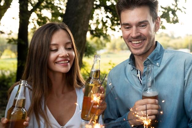 Amigos ao ar livre no parque tomando cerveja e se divertindo com espumantes