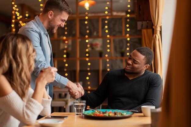 Amigos, apertando as mãos no restaurante