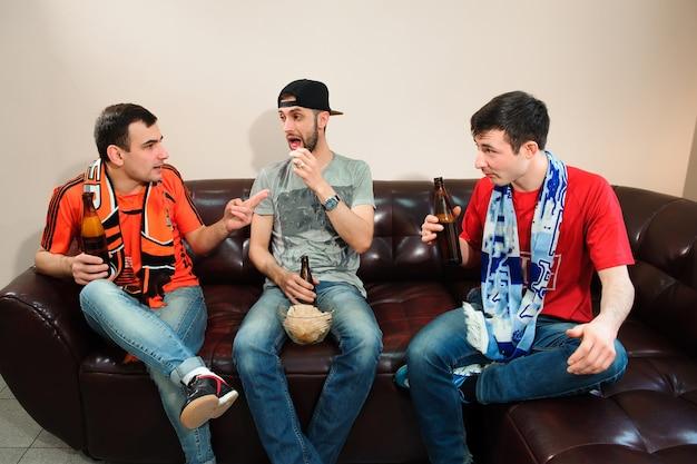 Amigos, aplaudindo e bebendo álcool enquanto assistia a partida de futebol