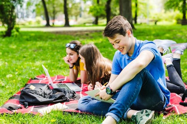 Amigos aprendendo a lição no parque Foto gratuita