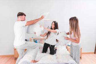 Amigos, aproveitando a luta de almofadas na cama no quarto