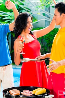 Amigos asiáticos, celebrando a festa na piscina para churrasco