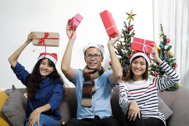 Amigos asiáticos em chapéus de santa que mostram caixas de presente na festa de natal.