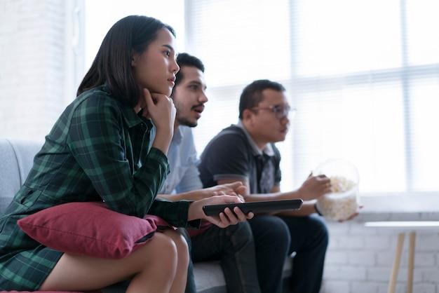 Amigos asiáticos estão assistindo tv em casa. eles entretêm