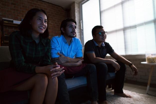 Amigos asiáticos estão assistindo tv em casa.