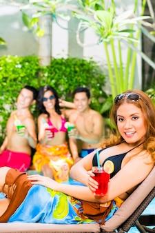 Amigos asiáticos festejando na festa da piscina no hotel