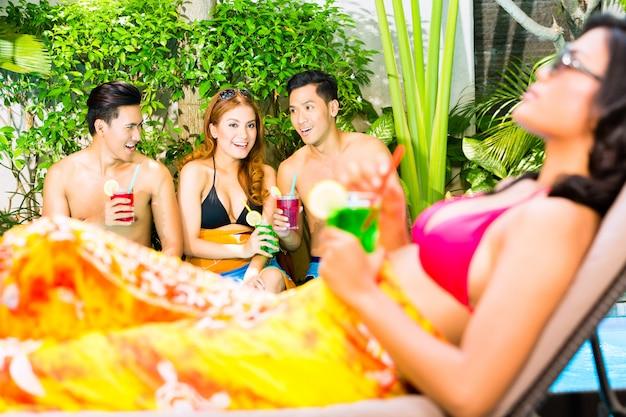 Amigos asiáticos festejando na festa da piscina no resort