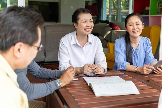 Amigos asiáticos idosos falando e usando telefone inteligente no lar de idosos.