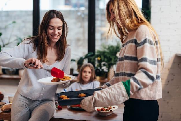 Amigos assam biscoitos e os transferem da bandeja para o prato.