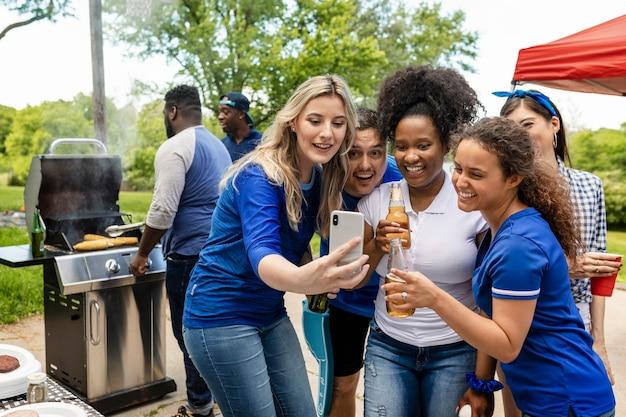 Amigos assistindo ao jogo em um telefone em uma festa ao ar livre