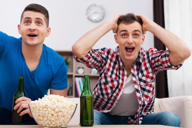 Amigos assistindo esportes na tv