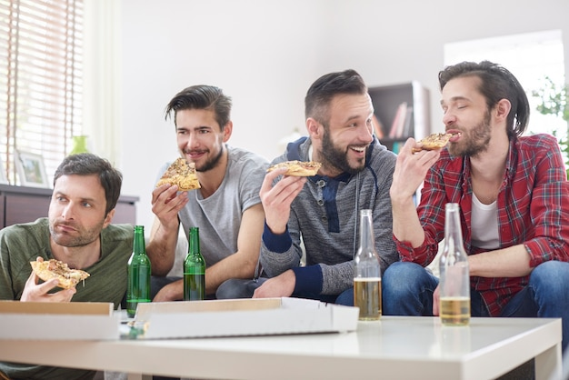 Amigos assistindo tv e comendo pizza