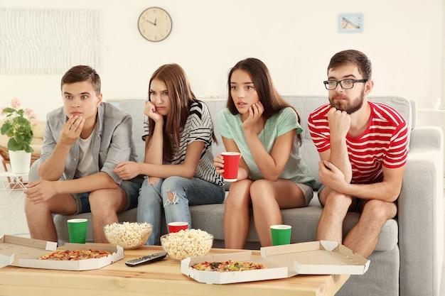 Amigos assistindo tv em casa