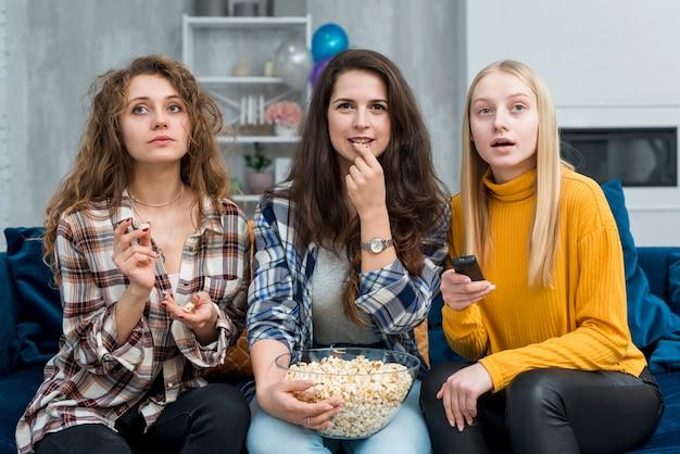 Amigos assistindo um filme enquanto come pipoca