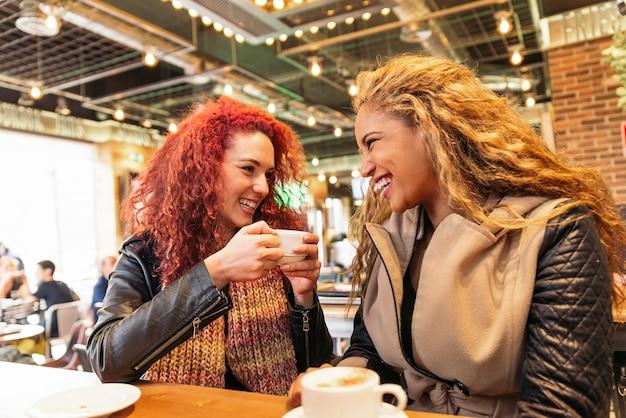 Amigos atraentes felizes no café desfrutando de um café