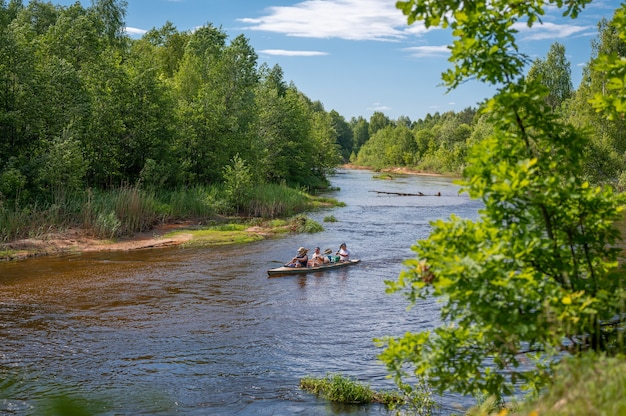 Amigos aventureiros canoando juntos em um belo rio em uma floresta densa. canoagem no belo rio na floresta. passeio de canoa no rio no verão
