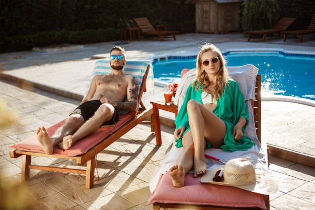 Amigos, banhos de sol, deitado nas espreguiçadeiras perto da piscina