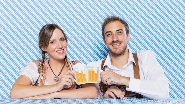 Amigos bávaros felizes com canecas de cerveja