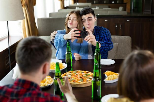 Amigos bebem cerveja, comem pizza, conversam e riem e tiram selfie na câmera do smartphone