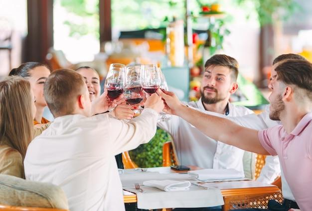 Amigos bebem vinho no terraço do restaurante.
