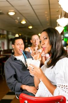 Amigos, bebendo batidos em um bar