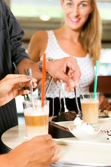 Amigos, bebendo café com leite e comendo bolo
