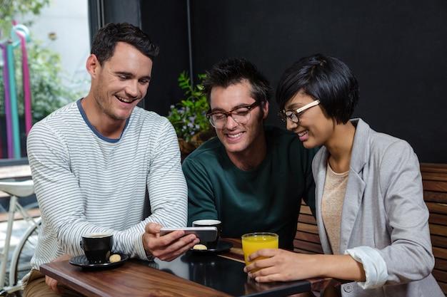 Amigos, bebendo café e suco de laranja enquanto olha para o smartphone