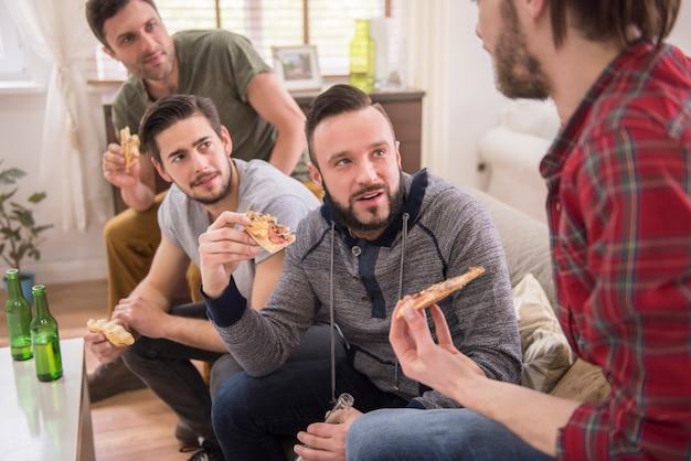 Amigos bebendo cerveja e comendo pizza