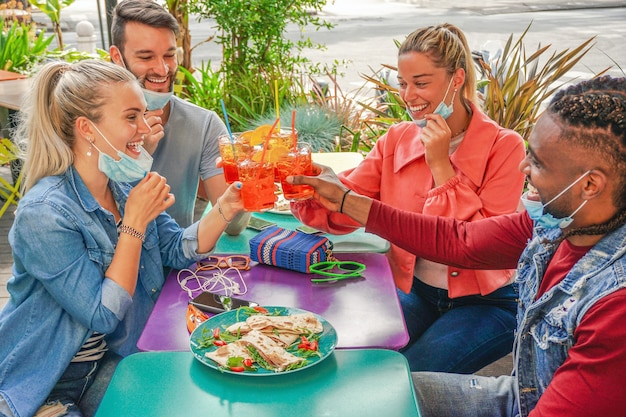 Amigos bebendo coktail e comendo petiscos de tapas em um bar de restaurante ao ar livre nos dias de verão com máscara facial para serem protegidos do coronavírus - pessoas felizes torcendo com spritz e se divertindo