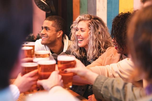 Amigos, bebendo e brindando com cerveja no pub