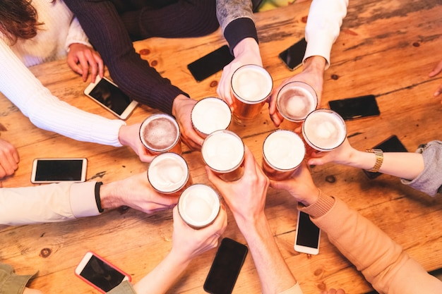 Amigos, bebendo, e, brindar cerveja, em, bar