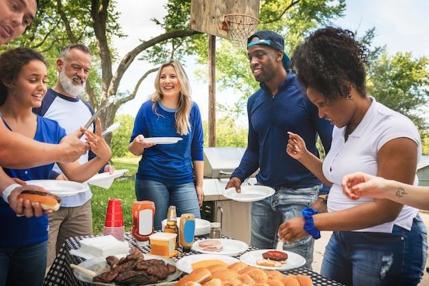 Amigos bebendo e comendo em uma festa ao ar livre