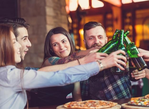 Amigos, bebendo e comendo pizzas em um bar