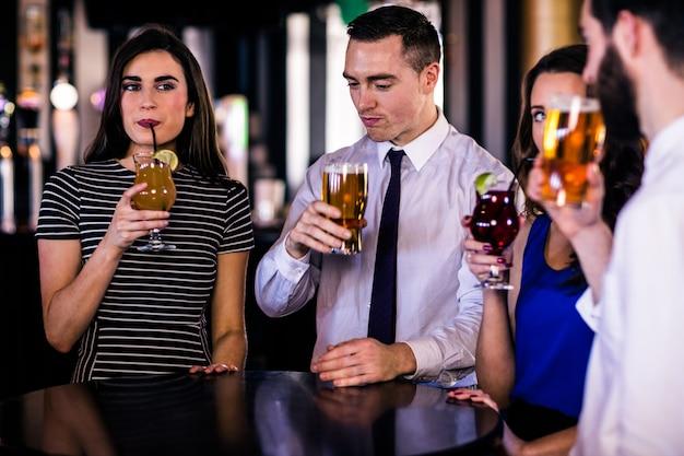 Amigos, beber cocktails e cervejas em um bar