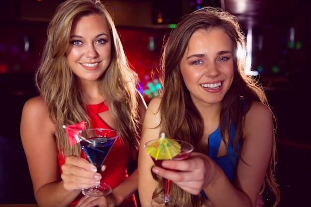 Amigos bonitos bebendo cocktails juntos